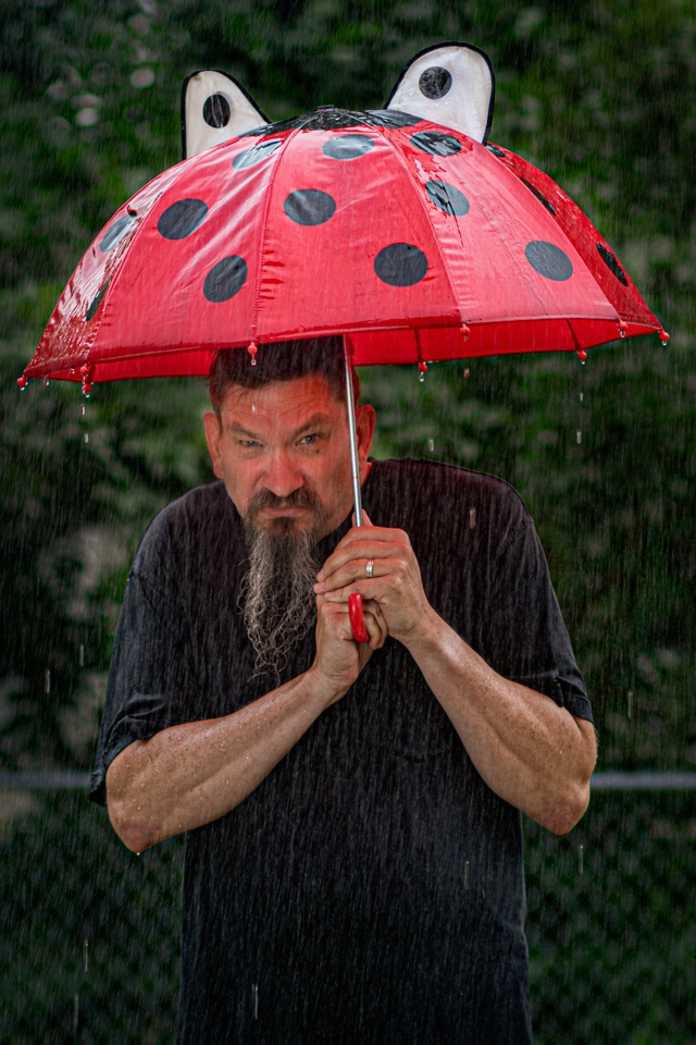 Grumpy man under ladybug umbrella - Dack Nehring - NMPC